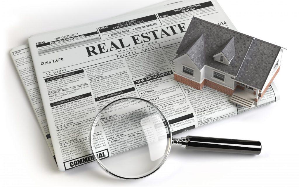 Real estate classifieds ads newspaper with house and magnifying glass isolated on white.